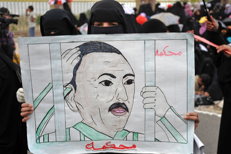 <p>A Yemeni anti-government protester holds a drawing calling for the trial of President Ali Abdullah Saleh during a demonstration in Sanaa. Now Saleh says he will step down.</p>