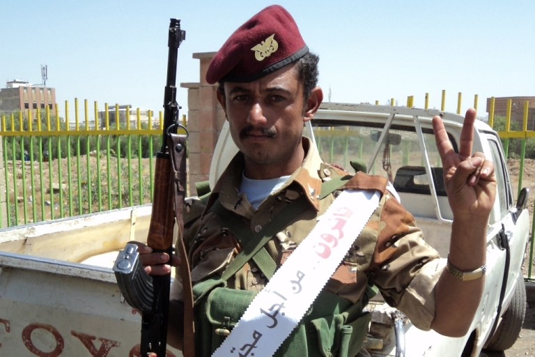 <p>A soldier loyal to General Ali Muhsin, who defected Monday, guards the protest camp. He's wearing a sash that says,