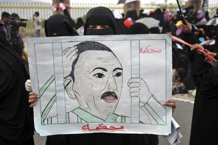 <p>A Yemeni anti-government protester holds a drawing calling for the trial of President Ali Abdullah Saleh during a demonstration in Sanaa. On October 8, 2011, President Salah said he would give up power in the coming days.</p>