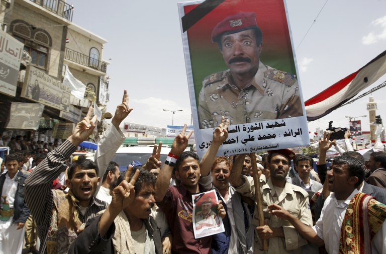 <p>Anti-government protesters shout slogans as they hold up an image of a killed soldier during a demonstration calling for the ouster of President Ali Abdullah Saleh in Sanaa on May 29, 2011, as dissident Yemeni generals accused the embattled president of surrendering the southern province of Abyan to 'terrorists' and called for more troops to defect.</p>