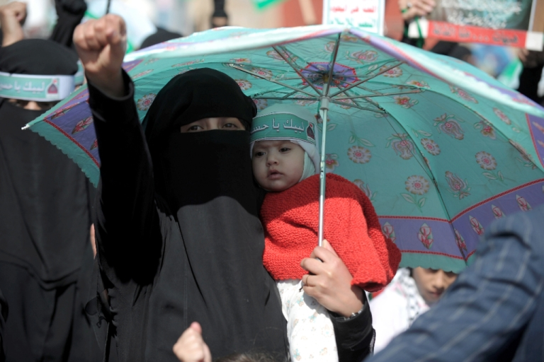 <p>A Yemeni Shiite woman holding a baby raises her fist as she takes part in a march during Ashura celebrations in Sanaa on November 24, 2012.</p>