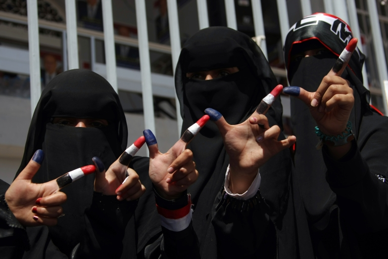 <p>Fully-veiled Yemeni women show the colors of the national flag on their forefingers during an election rally in support of the sole presidential candidate Abdrabuh Mansur Hadi in Sanaa on February 20, 2012.</p>