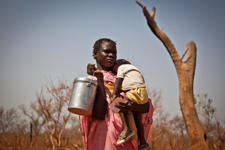 <p>Domestic violence is often a serious threat to women refugees in Africa, according to a new report by the International Rescue Committee. Here a displaced woman and her child from the Nuba Mountains in Sudan wait outside the Yida refugee camp registration center in Yida, South Sudan on April 26, 2012.</p>