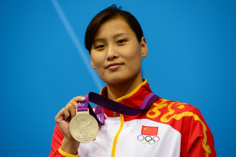 <p>China's silver medalist Lu Ying poses on the podium after the women's 100m butterfly final swimming event at the London 2012 Olympic Games on July 29, 2012 in London.</p>