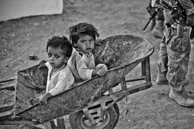 <p>In Sangsar, two little girls fidget in a wheelbarrow as soldiers question their uncle.</p>