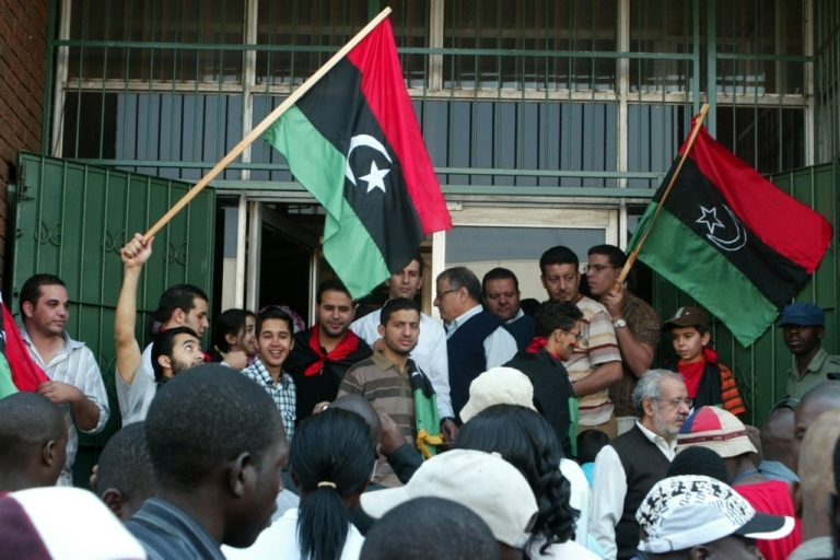 <p>Libyan embassy staff and Libyan nationals demonstrate outside the Libyan embassy in Harare on August 24, 2011. Libya's ambassador to Zimbabwe led a demonstration in which Libyans burned portraits of embattled leader Moammar Gaddafi and replaced Gaddafi's green flag with the old tricolor red, black and green flag from independence in 1951. The Mugabe government has ordered the deportation of the Libyan ambassador and others for these actions.</p>