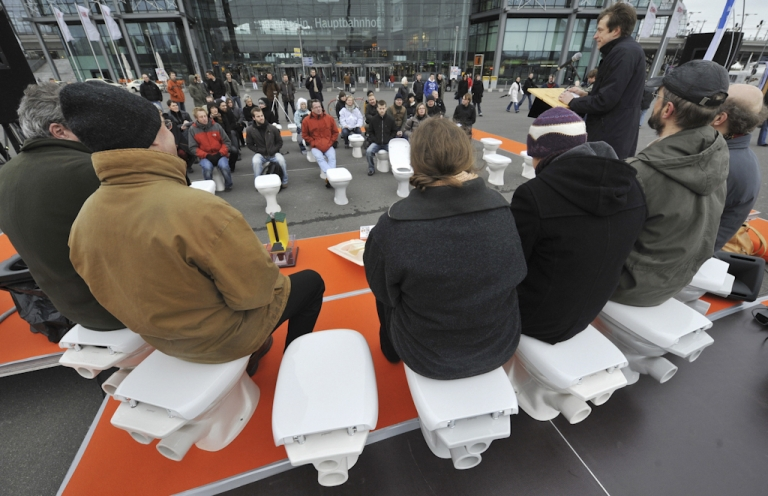 <p>Participants from various sanitation and hygiene concerns address a press conference while sitting on toilets in front of Berlin's central railway station on November 19, 2008, on the occasion of World Toilet Day.  The UN has established that some 38 percent of the world's population are living without adequate sanitation, and has called on governments to reduce that number by half by 2015.</p>