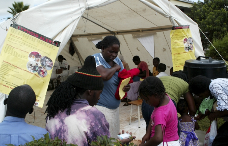 <p>Patients receive medication at a typhoid screening and treatment centre setup in a temporary tent at a clinic in the Kuwadzana township, on January 24, 2012, in Harare, Zimbabwe. Doctors reported at least 800 cases in a typhoid outbreak in the Zimbabwean capital.</p>