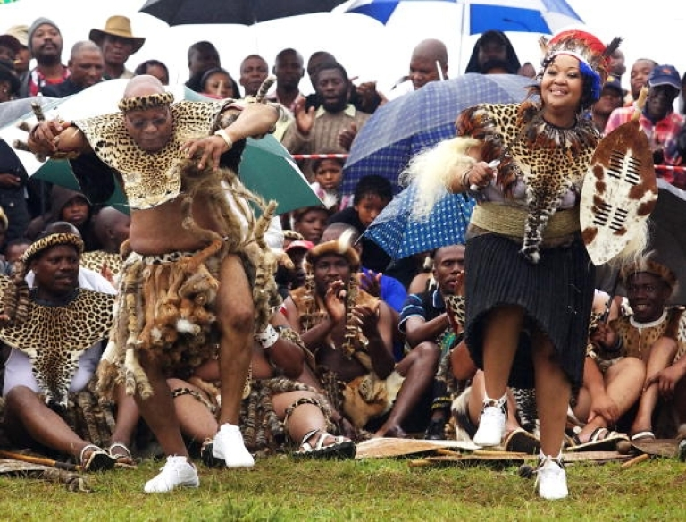 <p>South African President Jacob Zuma (L) sings and dances with his newlywed Tobeka Madiba (R) at their wedding ceremony on January 4, 2010 in a colourful Zulu traditional wedding outfit at Zuma's rural homestead of Nkandla, some 400 kilometres north of Durban. Wearing leopard skins and carrying a Zulu shield, South Africa's polygamous President Jacob Zuma on married today for fifth time, in a traditional ceremony in his remote hometown. The 67-year-old and his new bride Thobeka Madiba, 30 years his junior, danced in an open field at his homestead in Nkandla, a village deep in the countryside of KwaZulu-Natal province.</p>