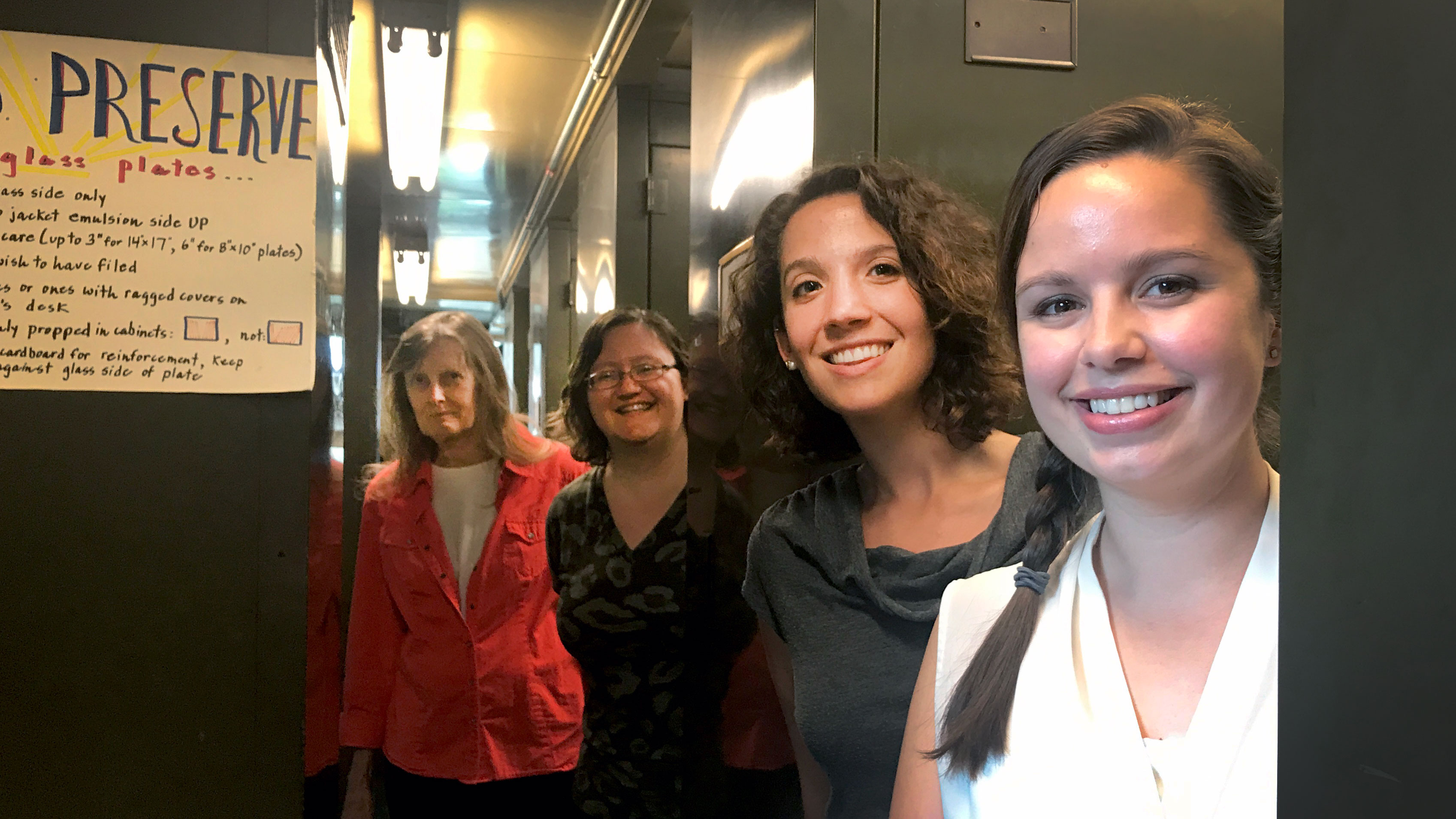 "A group of four women pose in the Harvard plate stacks, surrounded by tall metal cabinets. A paper sign to their left says ""preserve the glass."""